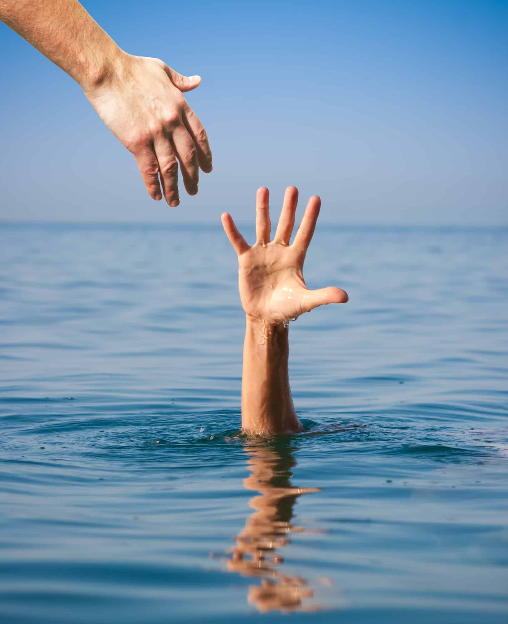 helping hand giving to drowning man in sea